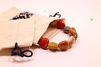 民族风布袋中的火山石花釉心形瓷珠手链