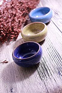 木板上的彩色冰裂纹陶瓷茶杯