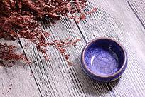 木板上的藏蓝色冰裂纹陶瓷茶杯