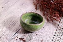 木板上的绿色冰裂纹陶瓷茶杯