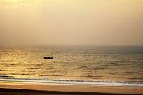 金色海面上小渔船