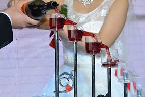 结婚仪式上新人往香槟塔上倒红酒