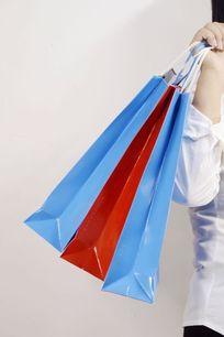 手提三个购物袋特写图