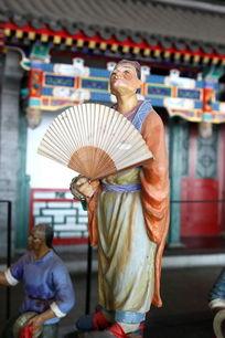 泥塑踩高跷扇纸扇子的人物雕像