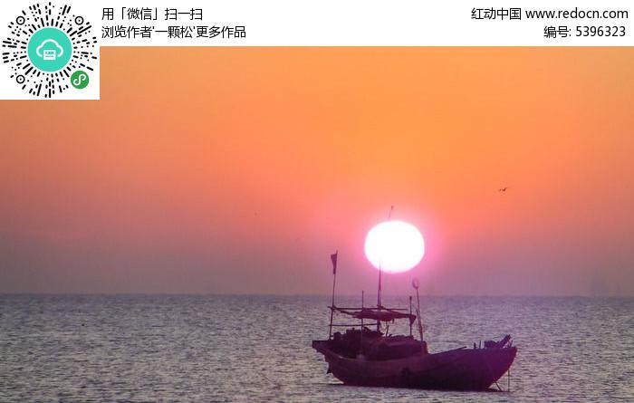 海上日出渔船航行图片