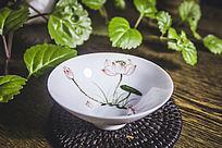 绿植旁的荷花水墨画白色茶杯