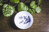 绿植旁的一个山水画花纹的白色茶杯