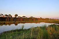 夕阳余晖笼罩下的水塘河流