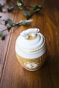 一只白底金色花纹的茶罐
