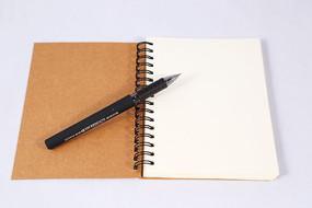白色翻页式笔记本上的圆珠笔