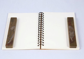 白色翻页式笔记本上的镇纸