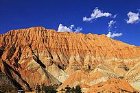蓝天白云下的红色山峰