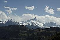 浅蓝天空下苍白的雪山