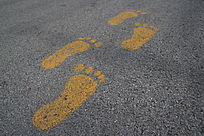 柏油马路上的黄色脚丫