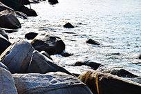 蓝色海边白色岩石浪花近景图