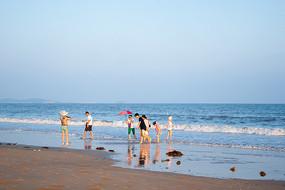 夕阳下金色沙滩上的游客