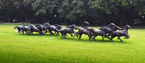 草地上的奔跑马群雕塑图片