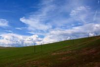 蓝天白云下的草场山坡