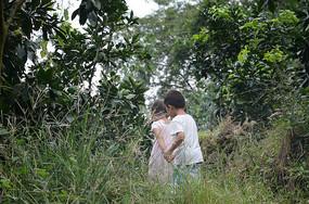儿童牵手爬山的背影