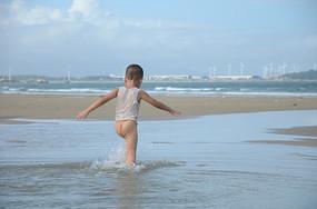 海边漫步戏水的小孩