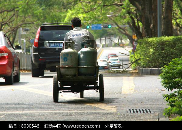 马路上骑着三轮车送煤气罐的送货工人背影图片