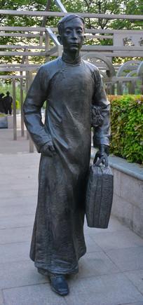 雕像手提行李箱的男子