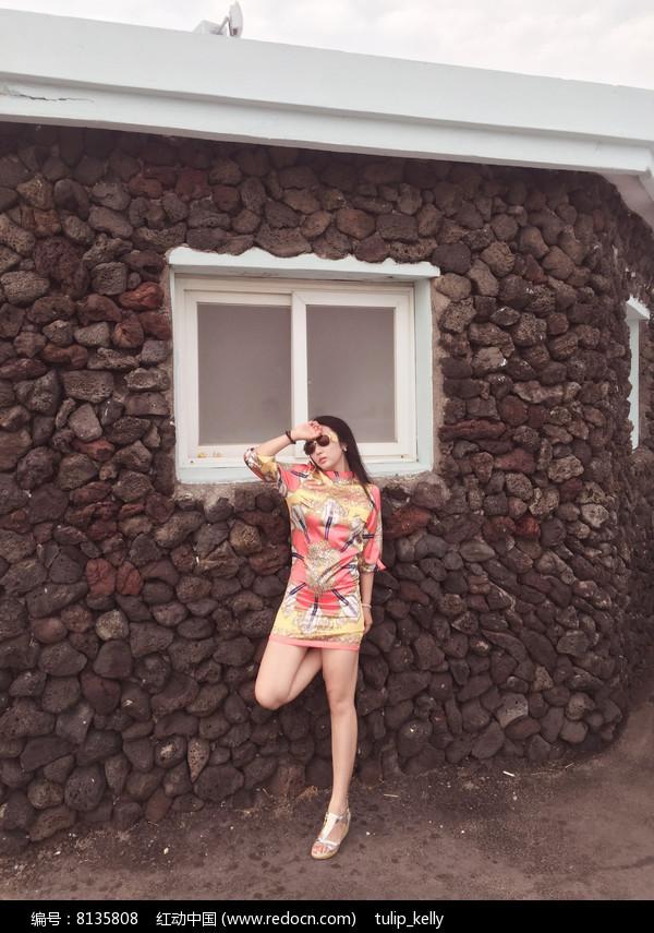 美女穿短旗袍戴墨镜站石屋墙旁图片