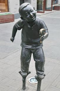 铜雕踩高跷摇拨浪鼓的小男孩