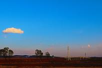 傍晚蓝色天空中的一朵白云与田野