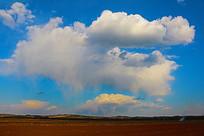 蓝色天空中云朵与田地