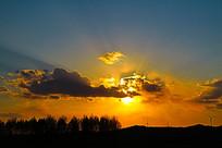 夕阳晚霞光芒中的树木山脉