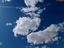 深蓝色天空上的几块白云图片