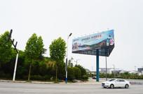 广告牌下行驶的轿车