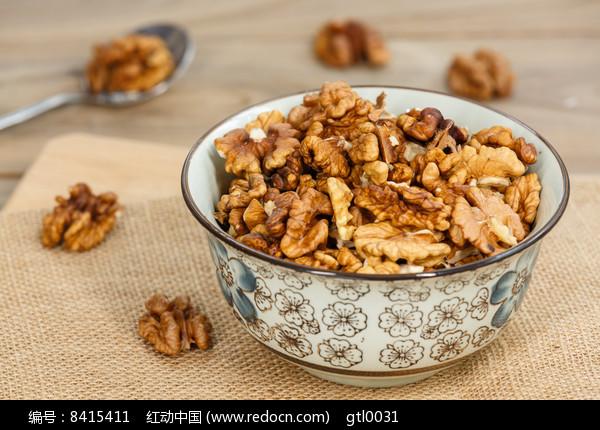 一碗核桃仁和勺子在木桌上