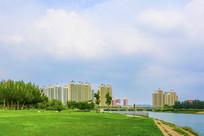 湾曲的河岸绿地与石桥高层建筑