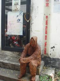 坐门前的人物雕塑