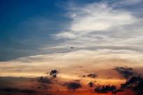 傍晚夕阳里穿越云层的飞机