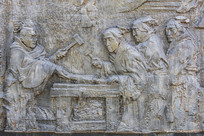 壁雕古代男人用锤锻打火上铁器