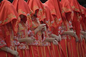 一排盖着红盖头的新娘子