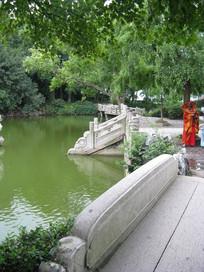 绿色池塘边的石护栏