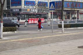 拎东西过马路的红衣女郎