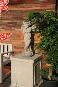 小天使塑像与绿色植物