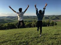 山顶上跳跃的情侣