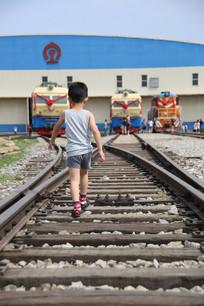 小男孩走在铁轨道路上