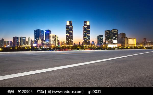 前景为沥青道路的郑州城市夜景图片