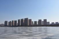 冰冻的河岸旁新建的排排楼房