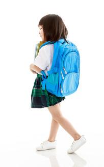白背景前背书包抱书的小女孩