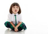 白色背景前坐在地上的小女孩