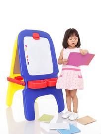 画板边手拿书阅读的小女孩