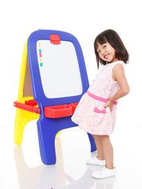 小女孩手叉腰开心站在画板前